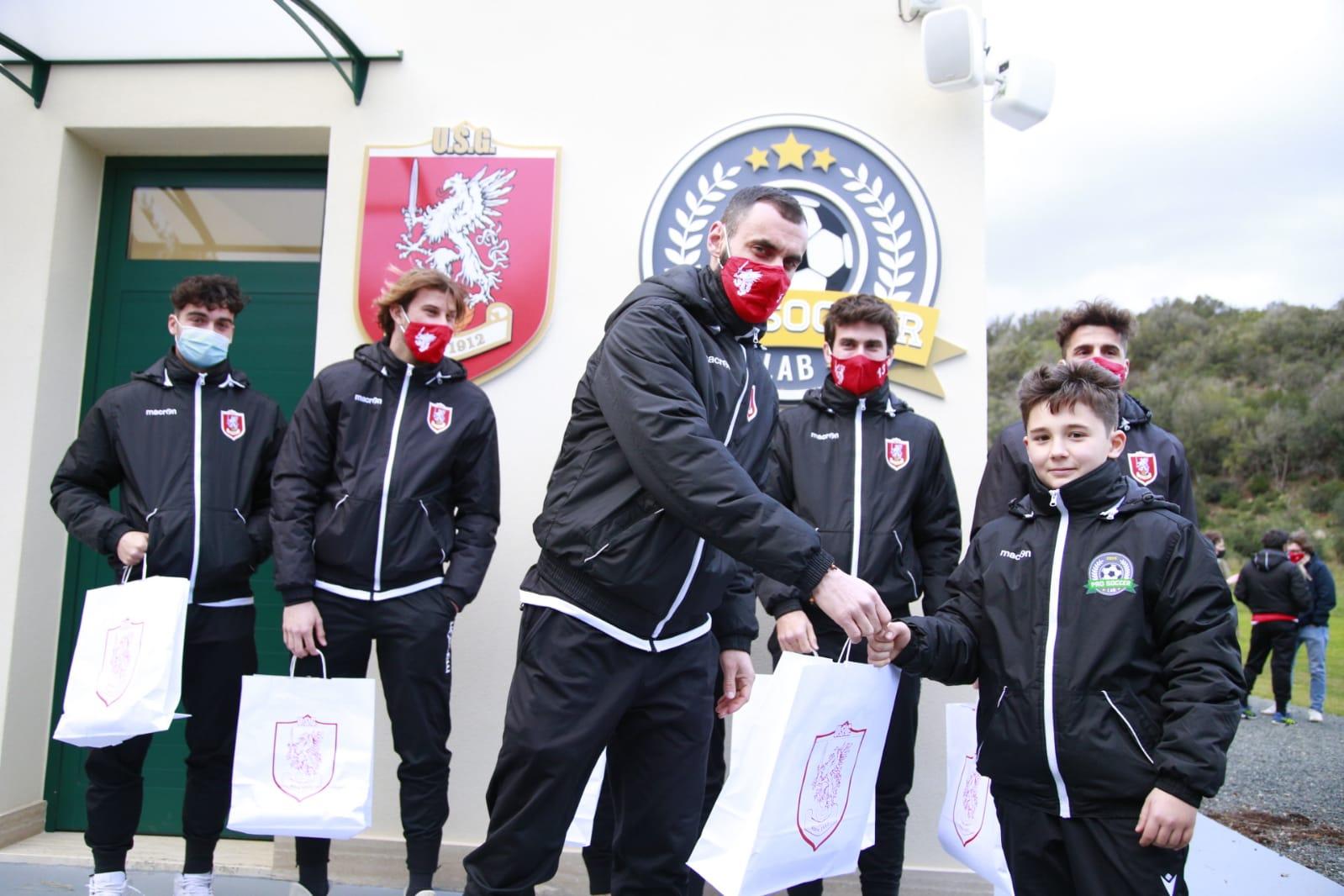 Il capitano dell'Us Grosseto, Andrea Ciolli, consegna i gadget unionisti a un campioncino della Pro Soccer Lab (foto Us Grosseto)